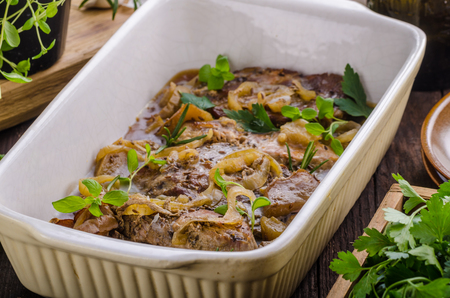 Pork chop in oven with apples, garlic herbs and onion Stock Photo