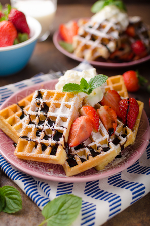 Waffles with berries, strawberries, chocolate on top and mint