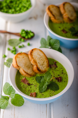 Pea soup, fresh herbs and bacon, food photography