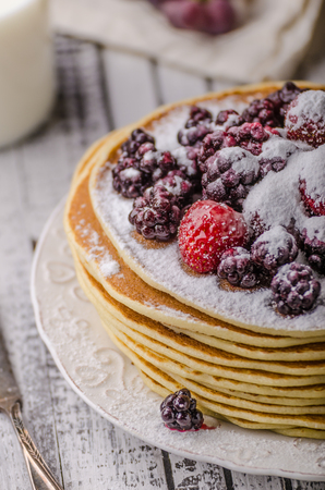 Homemade crepes with frozen berries, topped sugar, rustic wood board