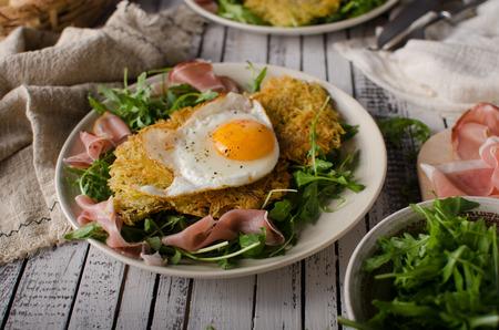 Potato pancakes with eggs and ham, fresh arugula salad Foto de archivo