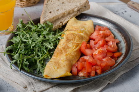 Perfect eggs omelette with vegetable salad, fresh arugula and juice