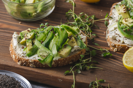 Delish fresh cheese on crisp bread, fresh cheese with avocado and cucumber and healthy seeds on top