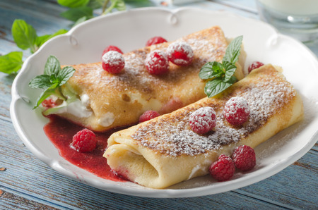 Delisious dessert with fresh fruit, mint and cheese filling inside crispy pancake