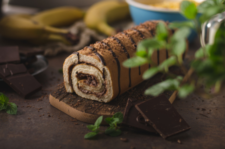Delish dessert with dark chocolate and sweet banana inside with fresh herbs as decoration