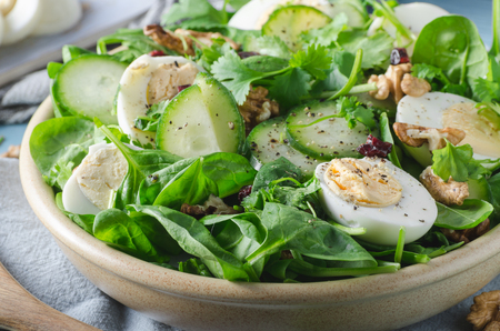 Delicious and simple healthy salad with nuts, eggs and cucumber