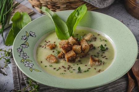 Delicious homemade soup from bear garlic, fresh herbs and crispy bread croutons