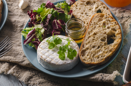 Delicious cheese, fresh salad and herbs with honey Stock fotó