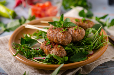 Hot and spicy delicious meat, grilled with fresh garlic and herbs, fresh salad