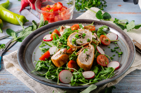Delicious chicken roulade filled with herbs and ham, fresh salad with radishes