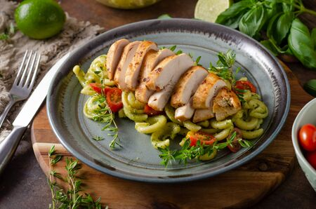 Delicous grilled chicken with fresh pasta with basil pesto and cherry tomatoes