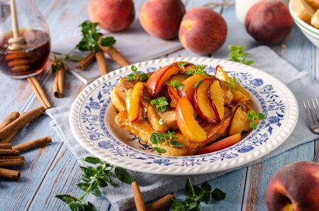 Delicious dessert with fresh peaches, roasted with maple syrup and french toast
