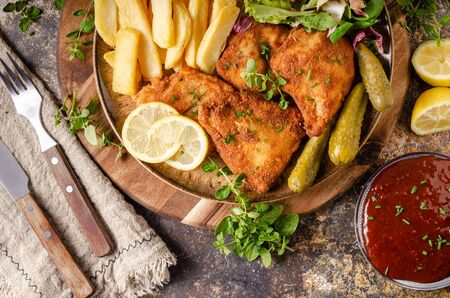 Delicious breaded meat with french fries, salad, pickless and beer