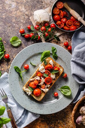 Fresch and simple breakfast with grilled tomatoes, crispy bread and basil