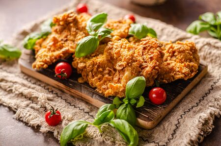 Delicous chicken steak in spicy cornflakes butter, bio herbs and ketchup