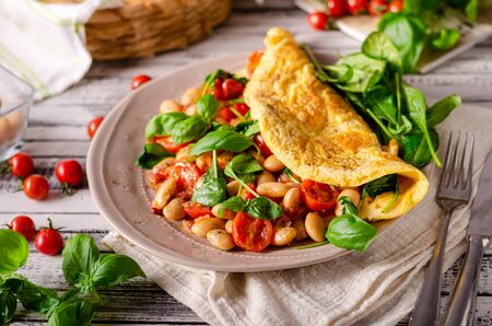 Heathy omelette with tomatoes, fresh herbs and beans, french onion Imagens