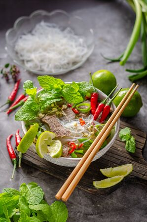 Traditional Vietnamese soup with chilli, noodles, fresh herbs and beef meat