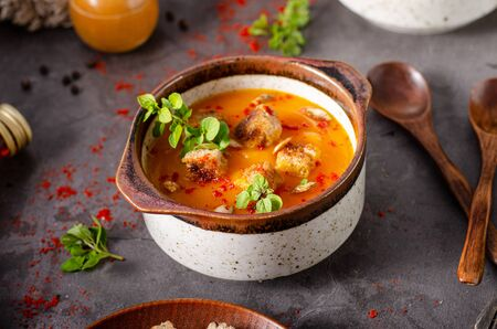 Sweet and spicy soup with crispy bread and fresh herbs