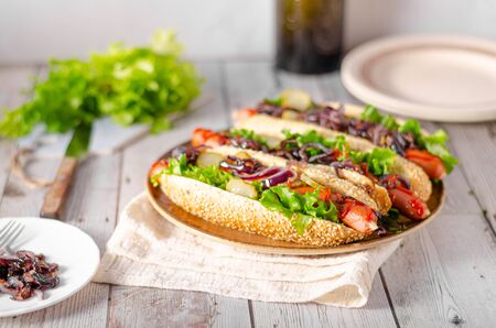 Hot dog with red onion, pickles and fresh salad