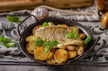 Delicious fish with roasted potatoes and bio garlic
