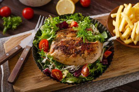 Ensalada fresca con tomates, pollo a la parrilla y papas fritas caseras