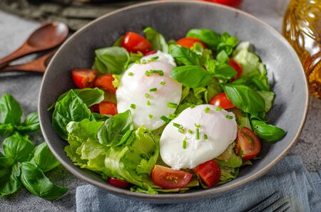 Fresh salad with egg benedict, tomatoes and delish sauce Standard-Bild
