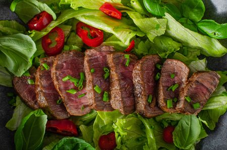 Delicious beef steak with salad, herbs and chilli
