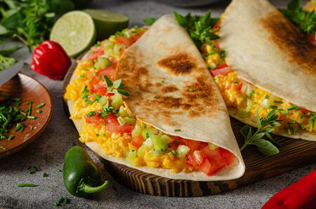 Fresh scrambled eggs with crispy tortillas, cheese, herbs and vegetable