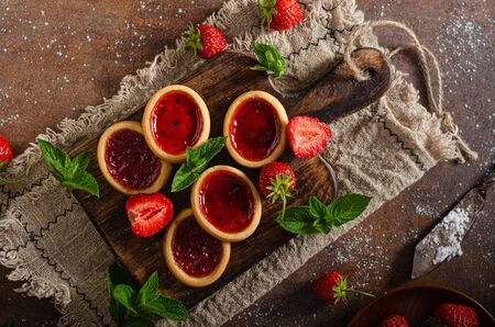 Delicious crispy tartlets with fresh strowberries jam and mint Standard-Bild