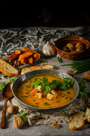 Creamy and delicious soup from roasted pumpkin, fresh herbs and crispy toast Standard-Bild