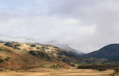 fells: A view of Fells in the English Lake District with a cloud and snow topped Hellvelyn in the distance