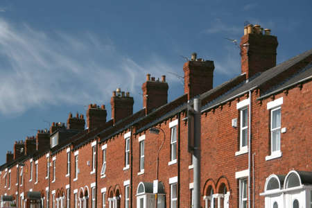 A row of terraced houses with beautiful whispy cloud background