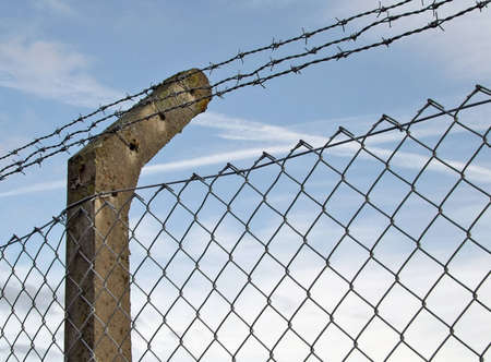 exclusion: Fence post supporting barbed wire and mesh Stock Photo