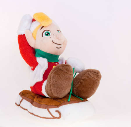 cuddly: A stuffed cuddly toy gnome in santa claus outfit on sledge Stock Photo