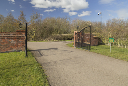 emphasis: An image of the gateway to the lodges at Eye Kettleby lakes. Shot near to Melton Mowbray, Leicestershire, England, UK. The emphasis of focus is on the gate and brick supports.