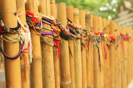 wristbands: Bamboo fence wrapped in wrist bands left by travellers in Thailand Stock Photo