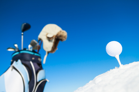 Tee golf ball and equipment in snowy landscape Фото со стока