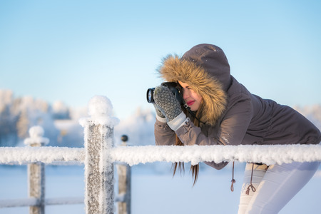 intent: Young woman taking a picture in winter. Stock Photo