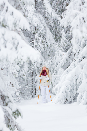 Young woman snowshoeing in snowy forest in winter Фото со стока