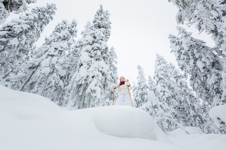 snowshoeing: Young woman snowshoeing in snowy forest in winter Stock Photo