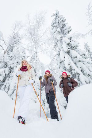 adults: Young adults snowshoeing in snowy forest in winter Stock Photo
