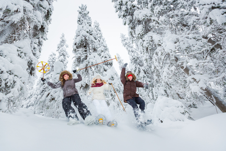 Young adults snowshoeing in snow covered forest in winter
