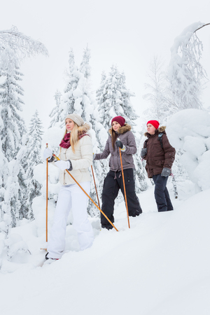 snowshoes: Young adults hiking with snowshoes in forest in winter Stock Photo