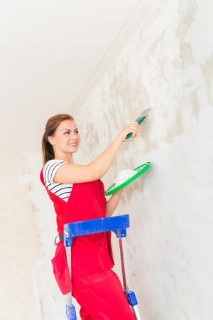 caulk: Young woman plastering concrete wall