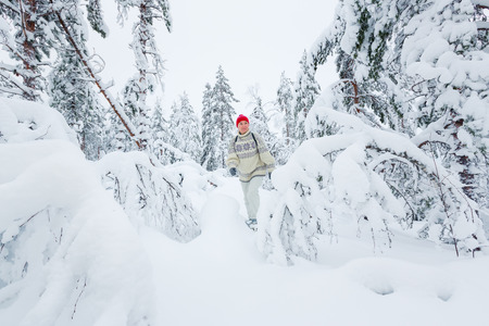 snowshoeing: Middle-aged woman snowshoeing in snowy forest in winter