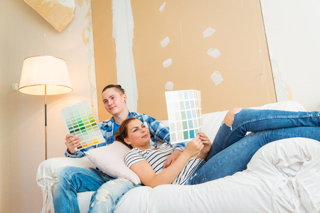 redecoration: Young couple planning renovation and choosing paint on the couch.