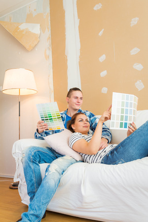 couple on couch: Young couple planning renovation and choosing paint on the couch.