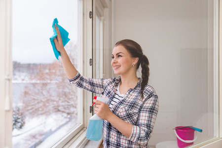 Smiling young woman cleaning windows in winter Stock Photo