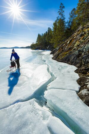 ice age: Middle age woman on ice with kick sledge Stock Photo