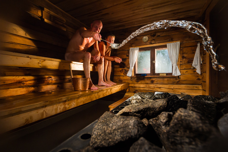 Middle aged couple in traditional wooden Finnish sauna, man throwing water to hot stove Imagens